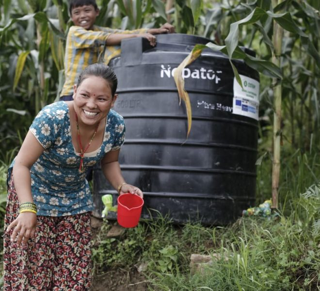 Woman and her son in Nepal getting fresh water from a black plastic drum