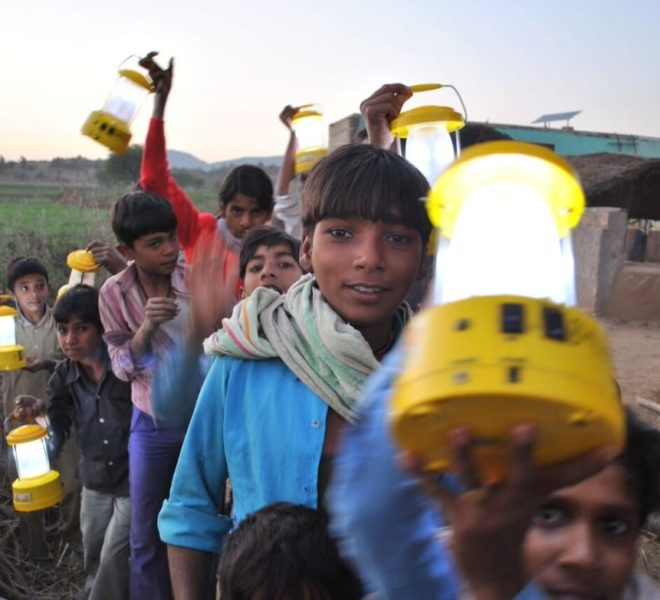 children holding up yellow electric lanterns