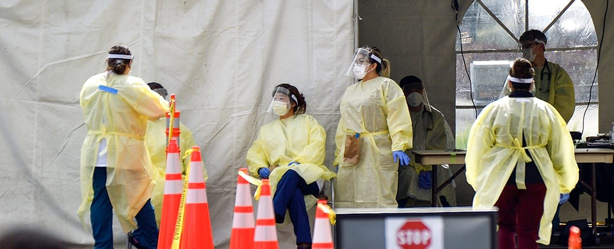 frontline healthcare workers in protective gear at a Covid-19 testing site