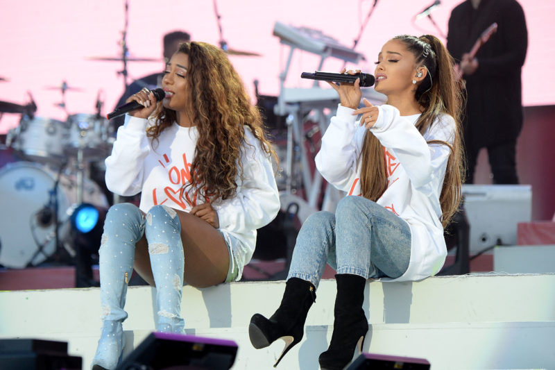Musicians Victoria Monet and Ariana Grande sit next to each other on a stage holding microphones to their mouths