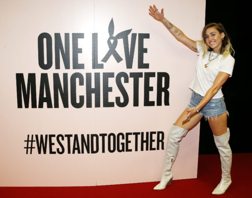 Actress Miley Cyrus stands nexts to a sign for the One Love Manchester concert