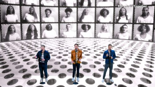 Platt Brothers sing into microphones surrounded by black-and-white CGI of a chorus of people