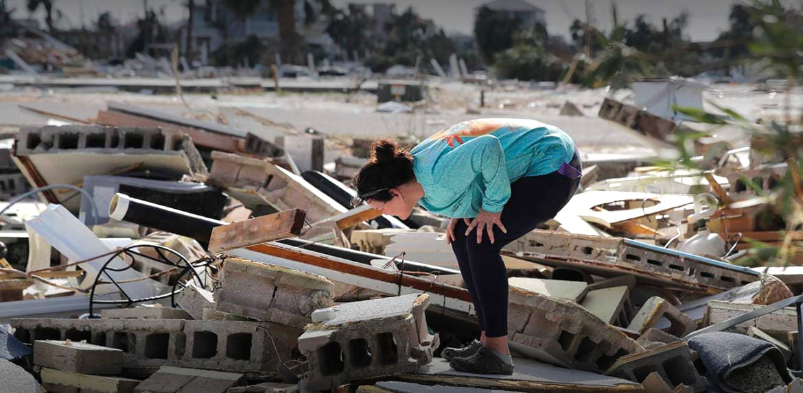 Woman looking through the rubble left after Hurricane Michael
