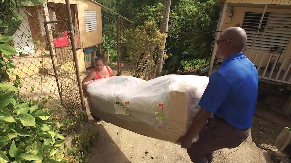 two people carrying a couch into a home after cleanup from Hurricane Maria