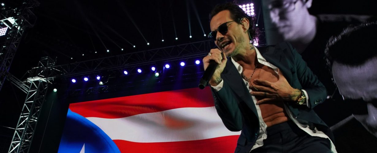 Musician Marc Anthony sings into a microphone with a Puerto Rican flag in the background
