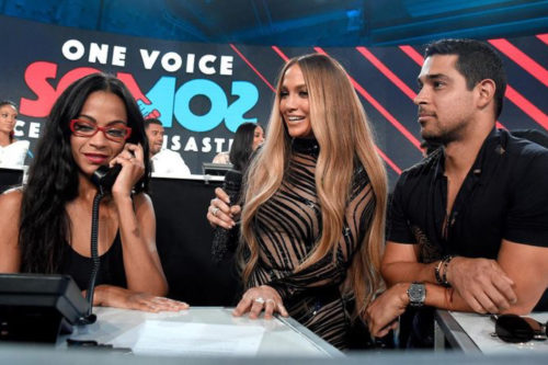 Zoe Saldana speaks into a phone with Jennifer Lopez and Wilmer Valderrama standing nearby