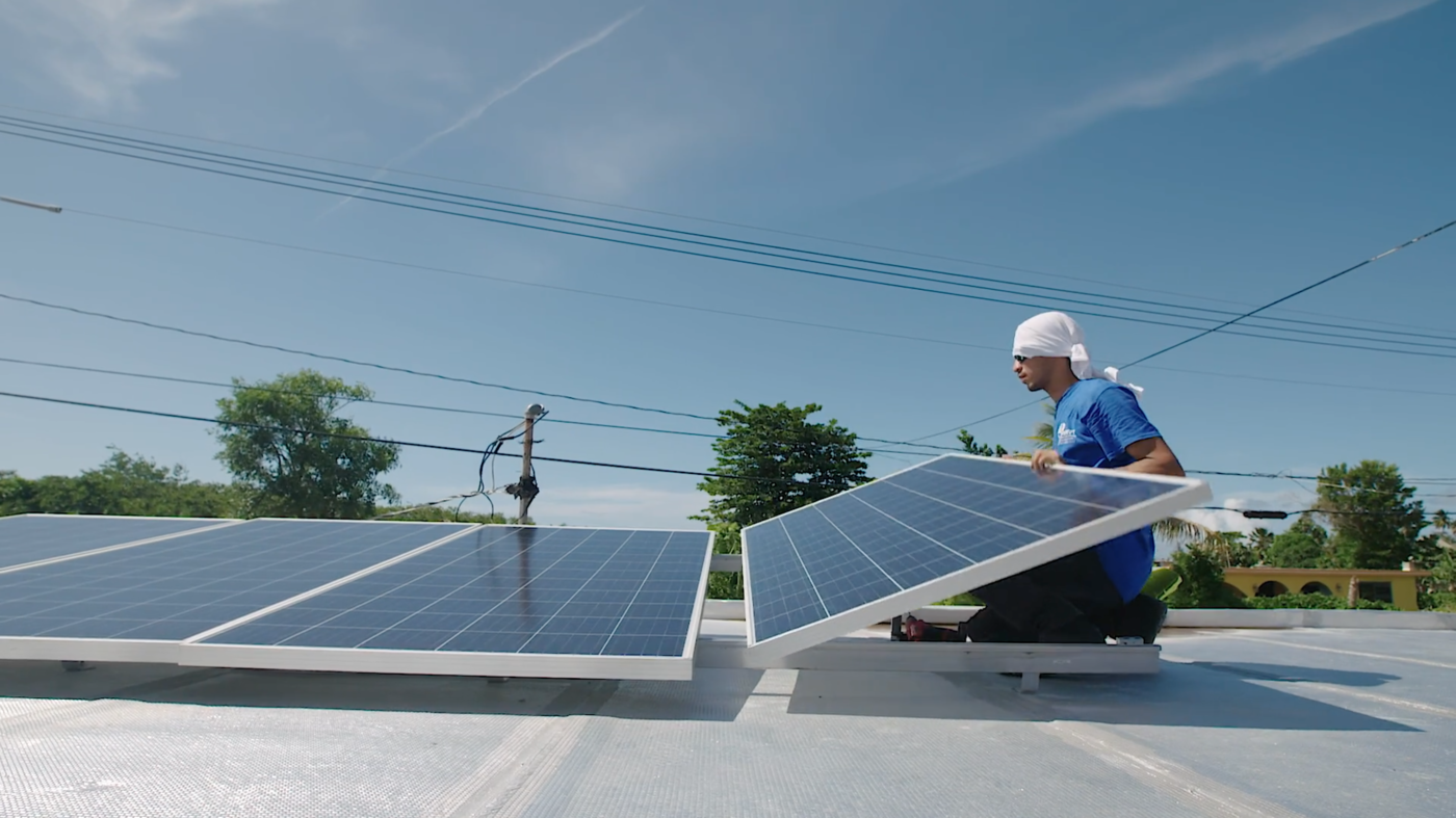 an Indesovi employee installs solar panels in a home in Puerto Rico