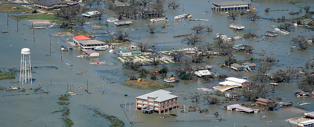 Floodwaters enveloping homes, roads, and trees
