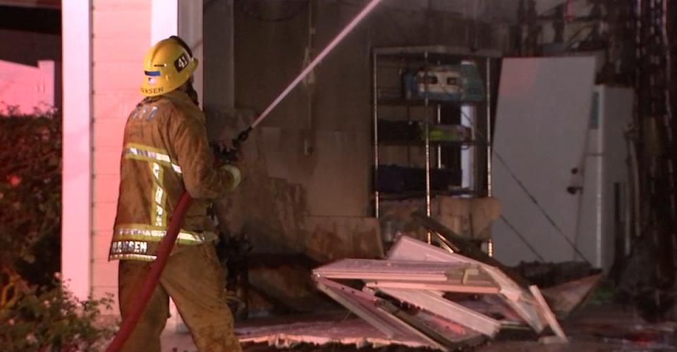 firefighter hosing off burning house